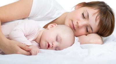 赤ちゃんとベッドで添い寝するママ