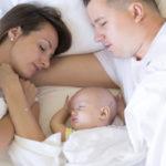 赤ちゃんとベッドで添い寝するパパママ