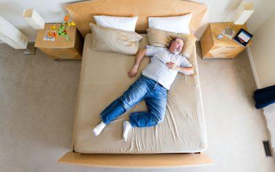 ベッドに斜めに寝る長身男性